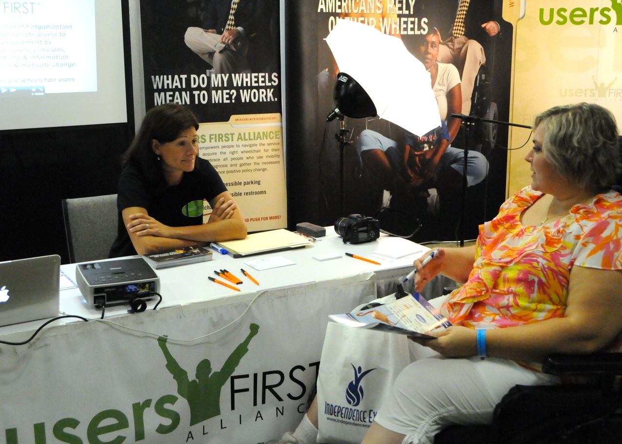 A wheelchair user speaks with a UsersFirst representative at a conference information booth.
