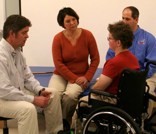 A wheelchair team comprised of a doctor, clinician, and supplier, all sit together speaking with a client.