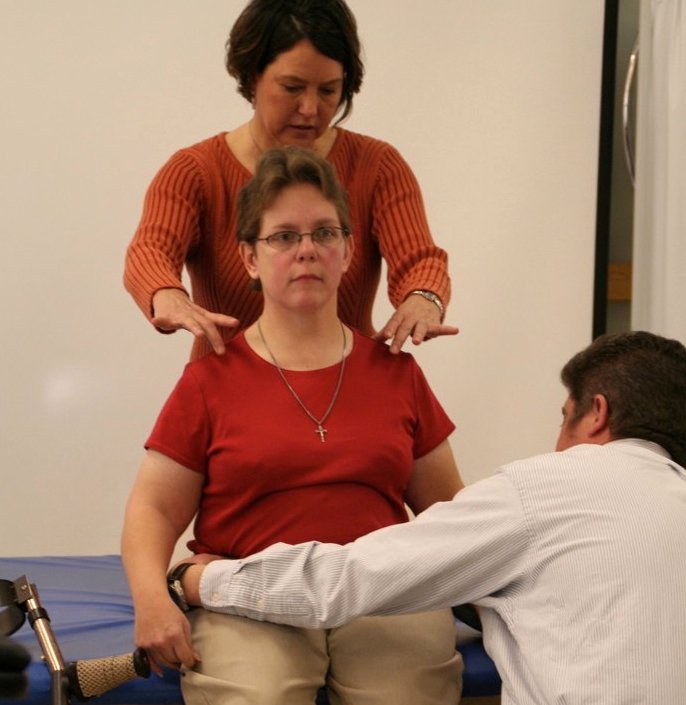 Two clinicians conduct a wheelchair assessment with a client.