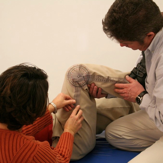 A client lays on a mat while two clinicians measure the knees' flexibility with a goniometer.