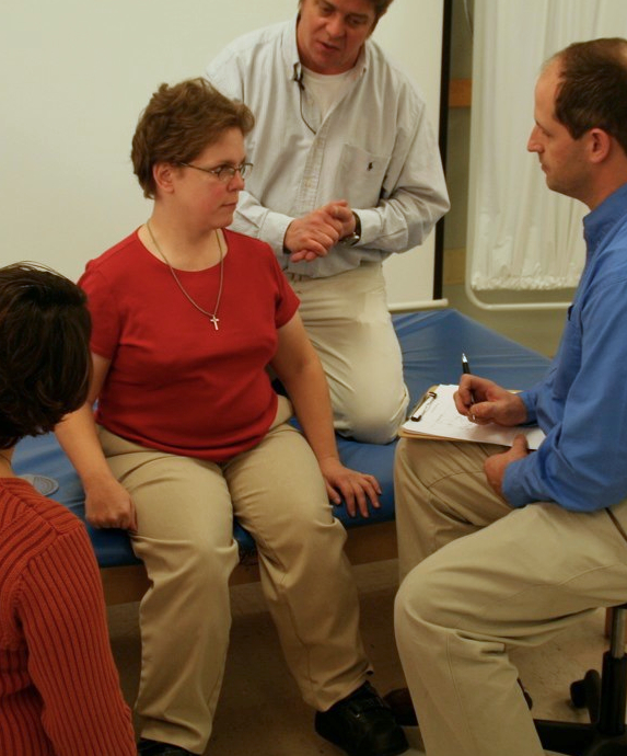 A woman sits on a mat at her Wheelchair Evaluation and Assessment surrounded by her wheelchair team and speaking with her medical equipment supplier who is taking notes on their conversation.