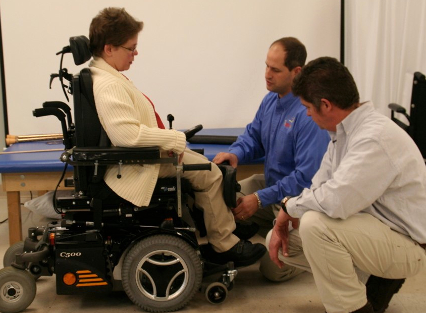 A woman meets with her clinician and supplier to assess the fit of her new wheelchair.