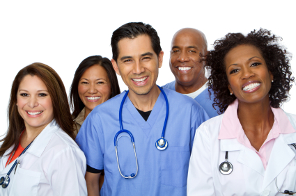 A group of female and male doctors of different ethnicities stand together in lab coats smiling.