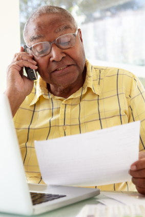 An older man reviews his personal insurance plan's paperwork while calling his insurer.