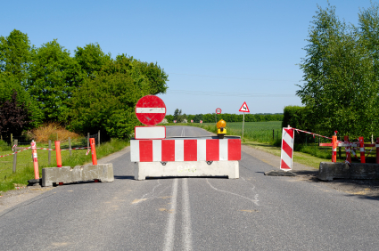 A warning sign and cement barrier block traffic from traveling down a road.
