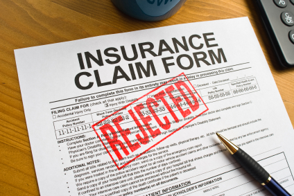 An insurance claim form is stamped with the word 'rejected.'