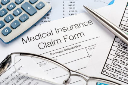 A medical insurance claim form sits on a desk with a pair of glasses and a pen waiting to be completed.