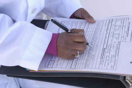 A seated doctor fills out a prescription form.