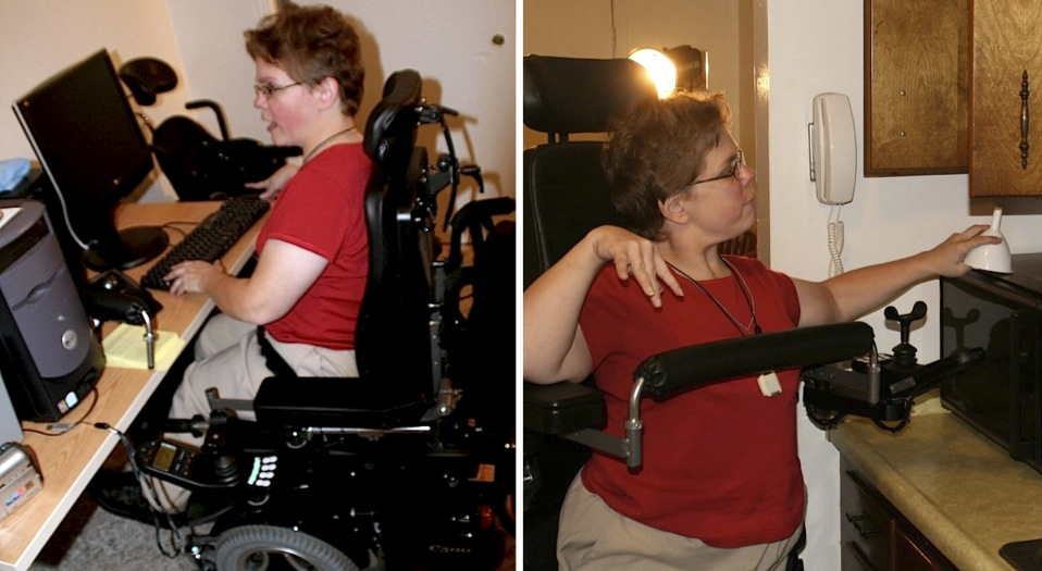 A woman navigates her home in her wheelchair sitting to use her home computer and moving into a standing position to reach high kitchen cabinets.