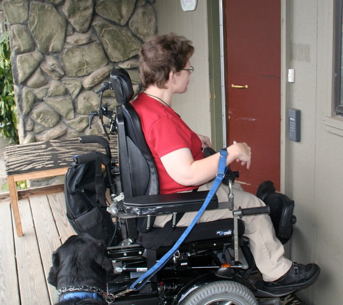 A woman enters her front door in her wheelchair with her guide dog.